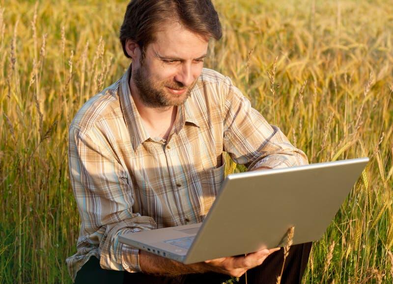 Современный фермер на пшеничном поле с компьтер-книжкой стоковая фотография rf