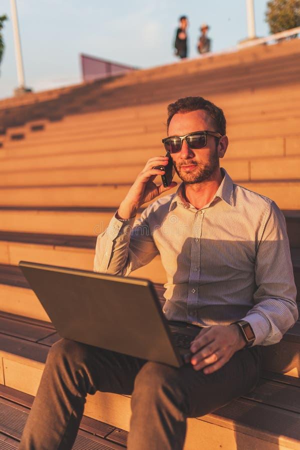 Современный фрилансер говоря на смартфоне и используя ноутбук пока сидящ на шагах на заходе солнца стоковое фото rf
