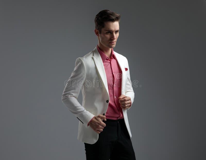 Современный человек в отверстии или закрывать костюма его куртку гостиной стоковая фотография