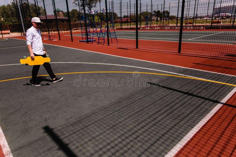 Современный человек в стильных прогулках носки на спортивной площадке спорта с желтым скейтбордом в руке стоковое фото