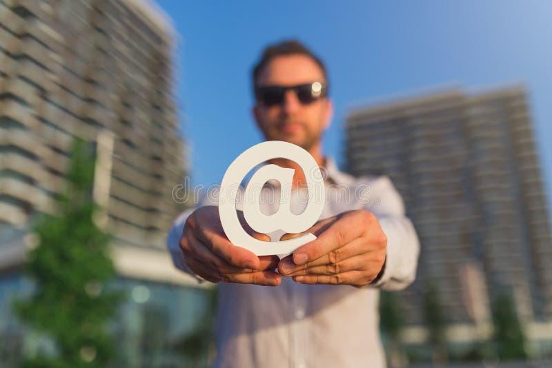 Современный человек дела держа деревянный символ электронной почты outdoors стоковые изображения