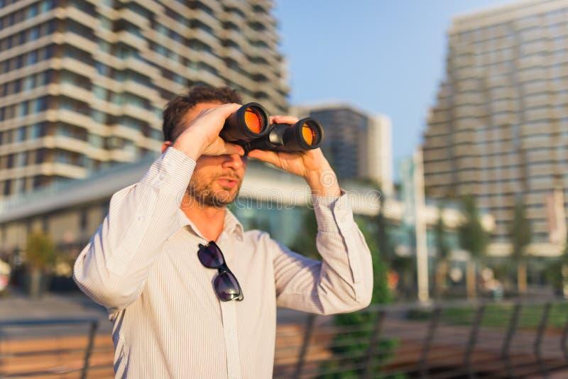 Современный человек используя бинокли outdoors стоковое фото