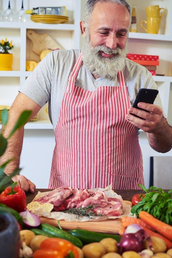 Современный человек используя телефон для того чтобы найти рецепт в интернете стоковое изображение rf