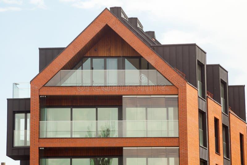 Современный экстерьер жилого дома в дневном свете с современным фасадом балкона и кирпича стоковое изображение
