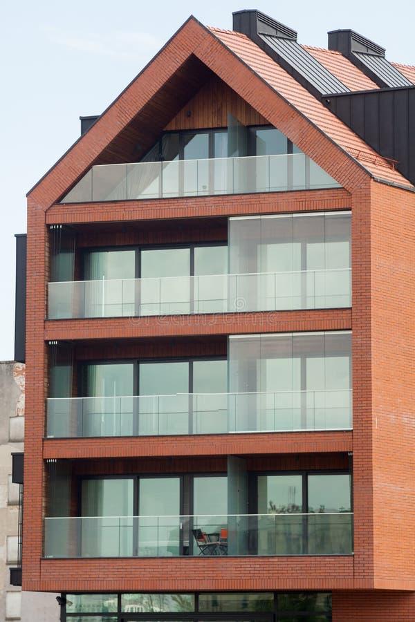 Современный экстерьер жилого дома в дневном свете с современным фасадом балкона и кирпича стоковые изображения
