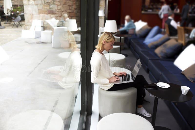 Современный keyboarding бизнес-леди на сет-книге пока работающ в интерьере студии просторной квартиры стоковое фото rf