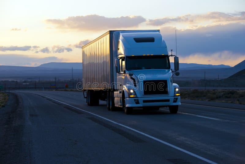 Современный semi трейлер тележки на twilight шоссе стоковое фото
