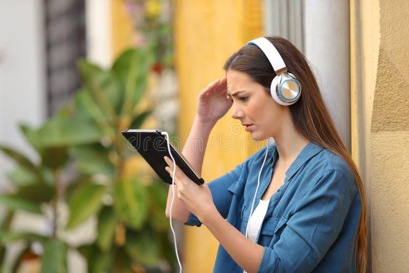 Содержание потревоженной девушки слушая и наблюдая планшета стоковое фото rf