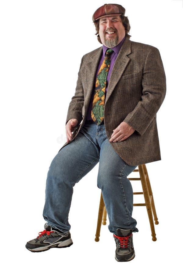 содружественный большой человек смеха сидит стоковое фото rf