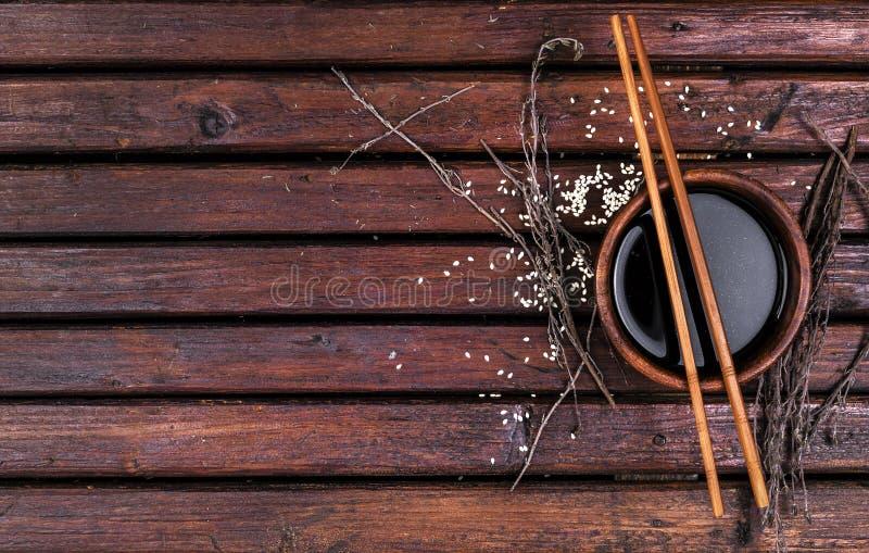 Соевый соус и палочки на деревянном столе стоковое изображение