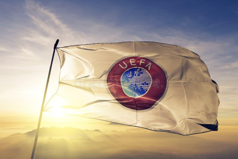 Соединение европейской ткани ткани ткани флага UEFA ассоциаций футбола развевая на верхнем тумане тумана восхода солнца иллюстрация вектора