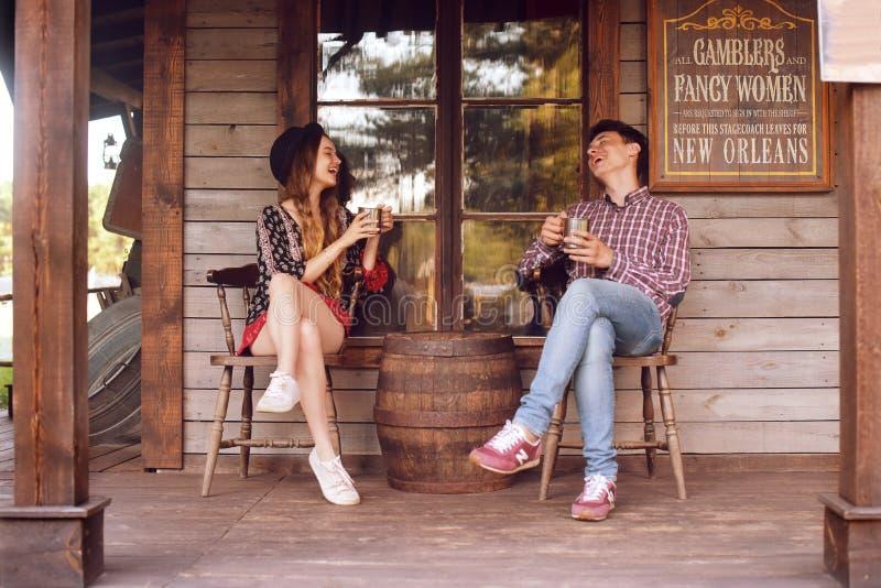 Соедините выпивая чай/кофе в Диких Западах, в западном доме Девушка в шляпе с длинными волосами Улыбка девушки и мальчика, смеясь стоковые фото