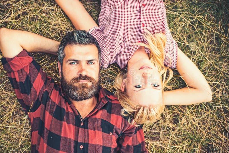 Соедините в любов лежа на траве в лесе или парке Романтичная дата в концепции природы, любов и отношения бородатый человек стоковые изображения