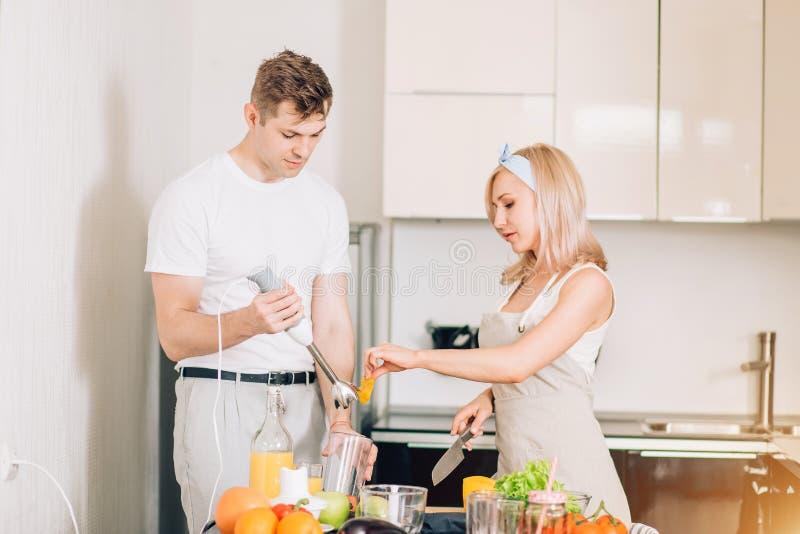 Соедините делать свежий органический сок в кухне совместно стоковые фотографии rf