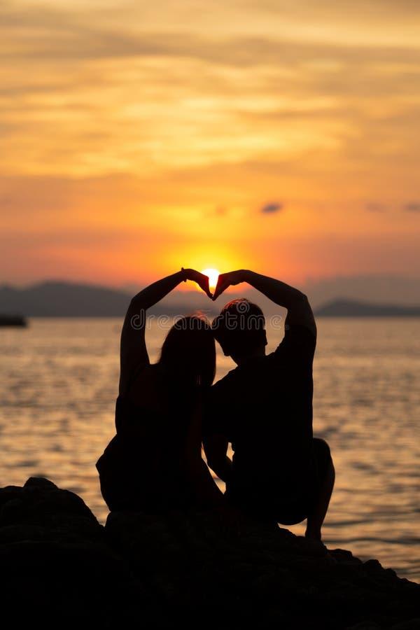 Соедините делать форму сердца на пляже в заходе солнца стоковое фото
