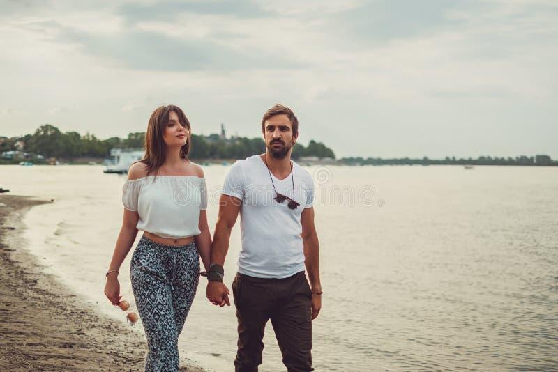 Соедините держать руки пока идущ на пляж стоковая фотография