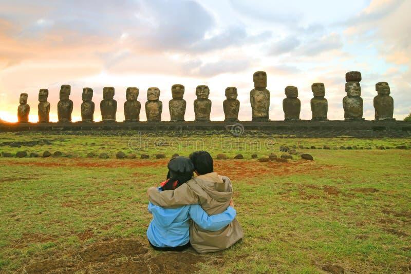 Соедините иметь счастливый момент перед внушительными статуями Moai Ahu Tongariki на восходе солнца, острове пасхи, Чили стоковые фотографии rf