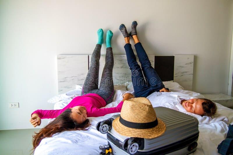 Соедините лежит на кровати с чемоданом Гонорары на концепции путешествием Подготовка багажа стоковое изображение rf