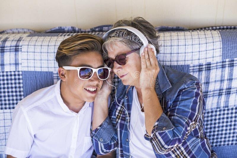 Соедините молодую и старое время семьи племянника бабушки и подростка совместно слушает музыка с наушниками и наслаждается днем t стоковое изображение rf