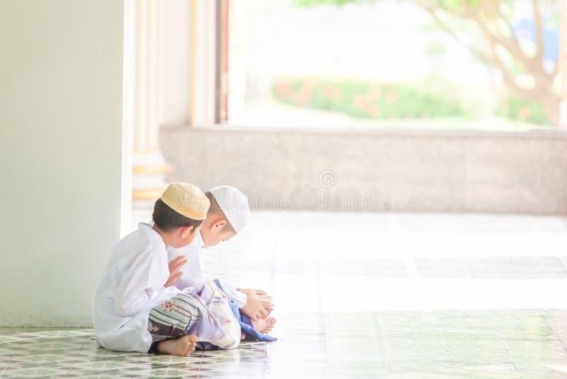 Соедините мусульманского мальчика в традиционной одежде читая Koran в m стоковые изображения