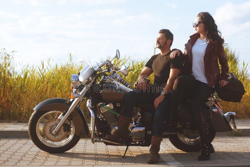 Соедините на предпосылке стоек поля около мотоцикла Путешествовать на велосипедах r Дата на заходе солнца красивом стоковое фото