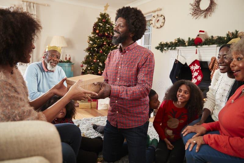 Соедините обменивать подарки как Multi поколение семья празднует рождество дома совместно стоковое изображение rf
