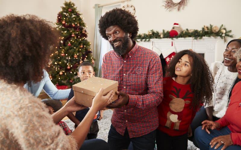 Соедините обменивать подарки как Multi поколение семья празднует рождество дома совместно стоковая фотография rf