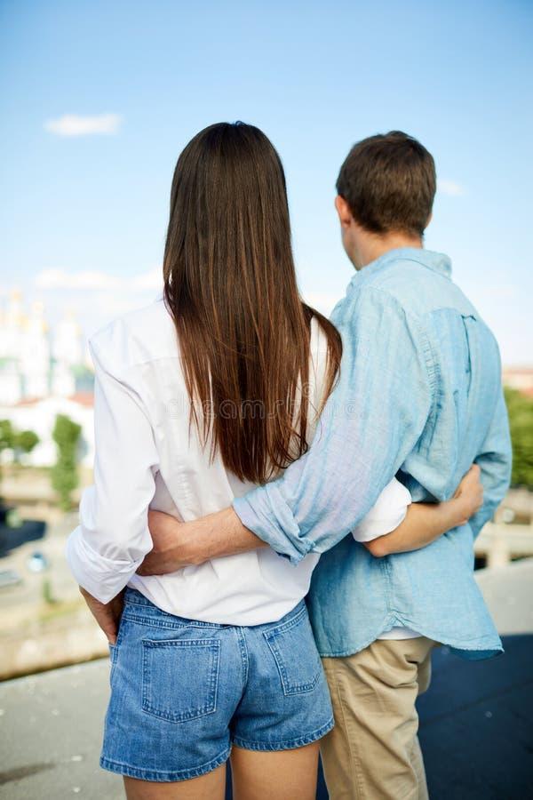 Соедините обнимать один другого и смотреть в расстояние стоковое изображение rf