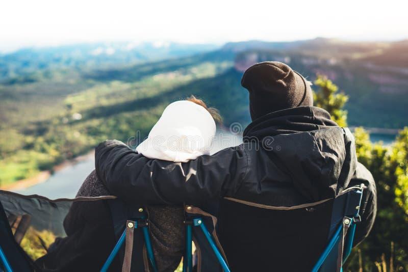 Соедините обнимать 2 романтичных люд прижимаясь и выглядя панорамный ландшафт горы пирофакела солнца, концепция выходных путешест стоковые изображения rf