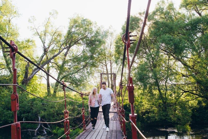 Соедините парня и девушки бежать на мосте над рекой стоковая фотография rf