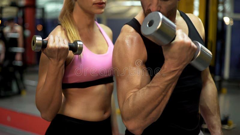Соедините поднимаясь гантели совместно в спортзале, парне показывая правильный путь сделать спорт стоковые изображения