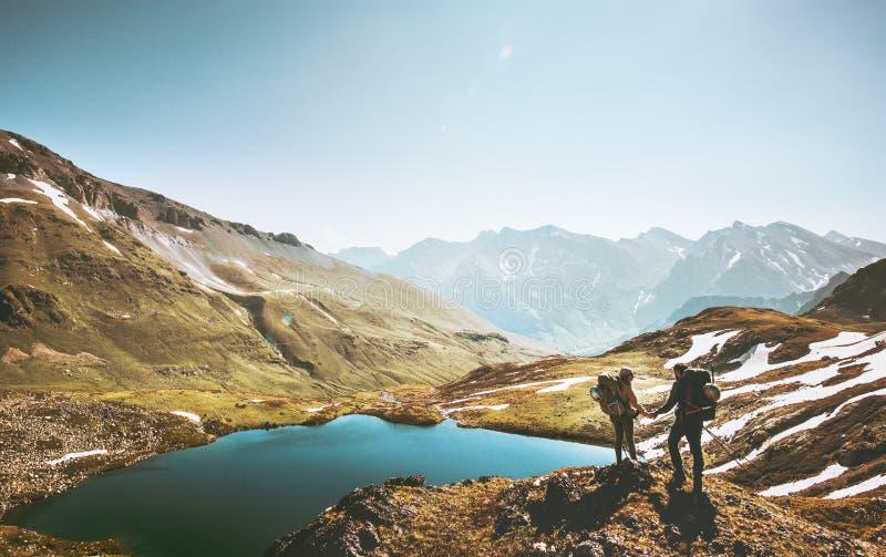 Соедините путешественников держа руки на скале горы над озером совместно стоковое фото rf