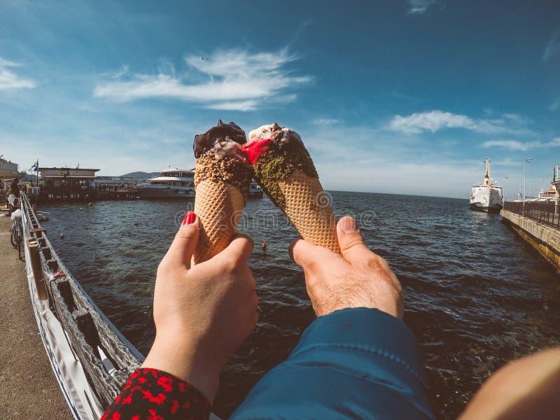Соедините руки держа плавя конус вафли мороженого в руках на предпосылке голубого неба и моря стоковое фото