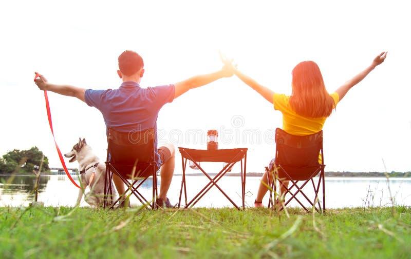 Соедините сидеть на горящем лагере с вашей собакой около реки на заходе солнца, поэтому насладитесь и счастливый солнечный день стоковое фото rf