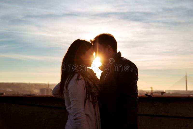Соедините смотреть один другого на крыше на заходе солнца стоковое изображение rf