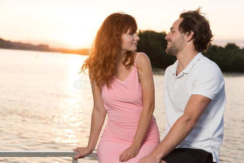 Соедините смотреть симпатичный на одине другого во время захода солнца на яхте стоковое фото rf