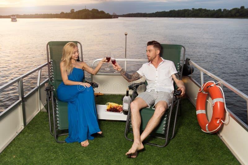 Соедините смотреть симпатичный на одине другого на яхте, и выпивая w стоковые изображения