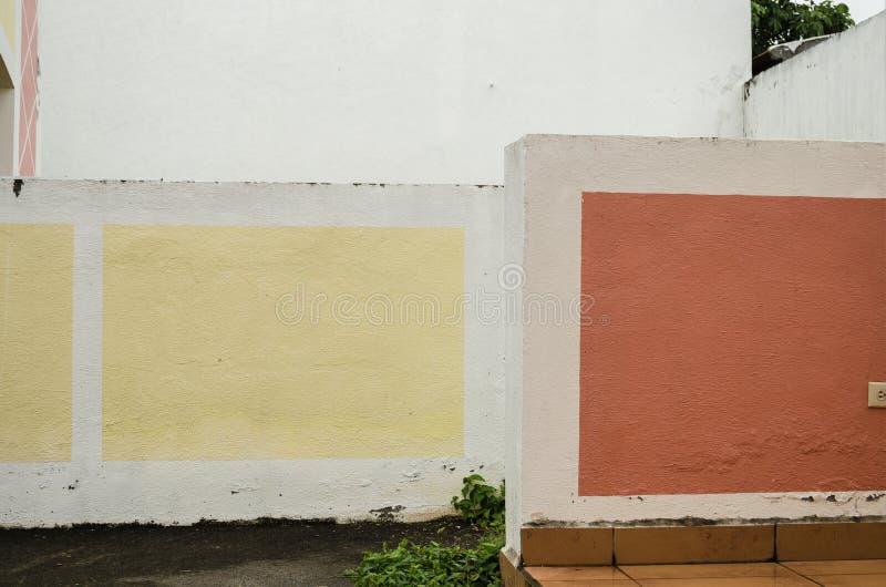 Соедините 2 стен цемента покрасил белый и украшенный с желтым и красными площадями, предпосылка пасмурного дня стоковая фотография rf