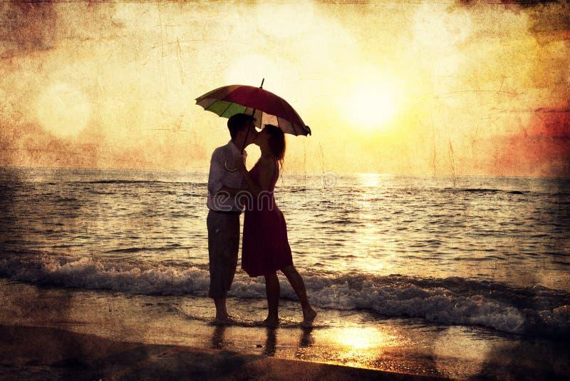 Соедините целовать под зонтиком на пляже в заходе солнца. Фото в o стоковые фото