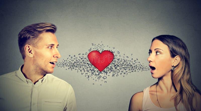 Соединение влюбленности Женщина человека говоря друг к другу красное сердце in-between стоковые изображения rf