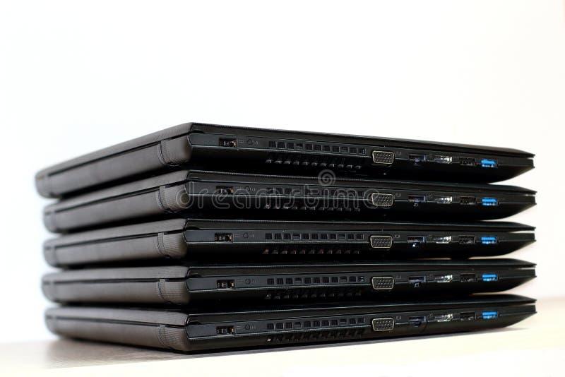 Соединение компьютера Сложенный стог компьтер-книжек на белой предпосылке стоковое изображение
