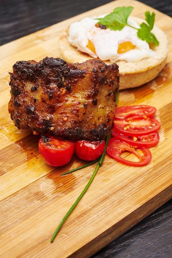 Соединение свинины служило с tomators и яичком младенца на деревянной доске стоковое фото rf