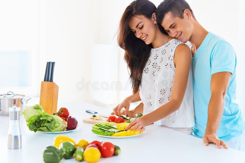 Соедините варить обедающий и усмехаться на камере Женщина режа v стоковые фотографии rf