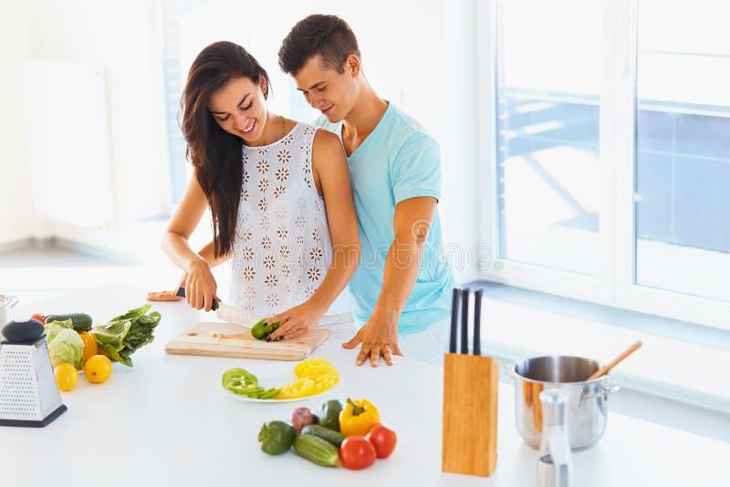 Соедините варить обедающий Овощи вырезывания женщины, человек обнимая h стоковая фотография