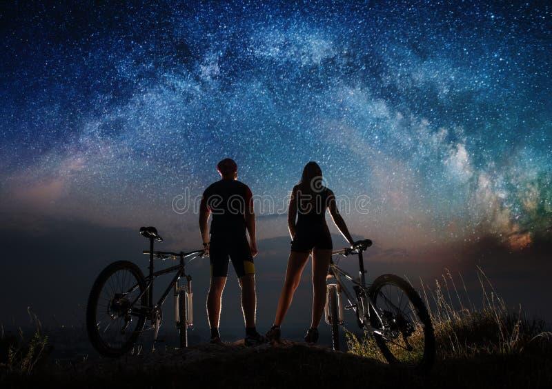 Соедините велосипедистов с горными велосипедами на ноче под звёздным небом стоковые фото