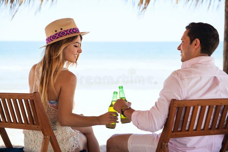 Соедините делать здравицу с пивом на пляже стоковая фотография rf