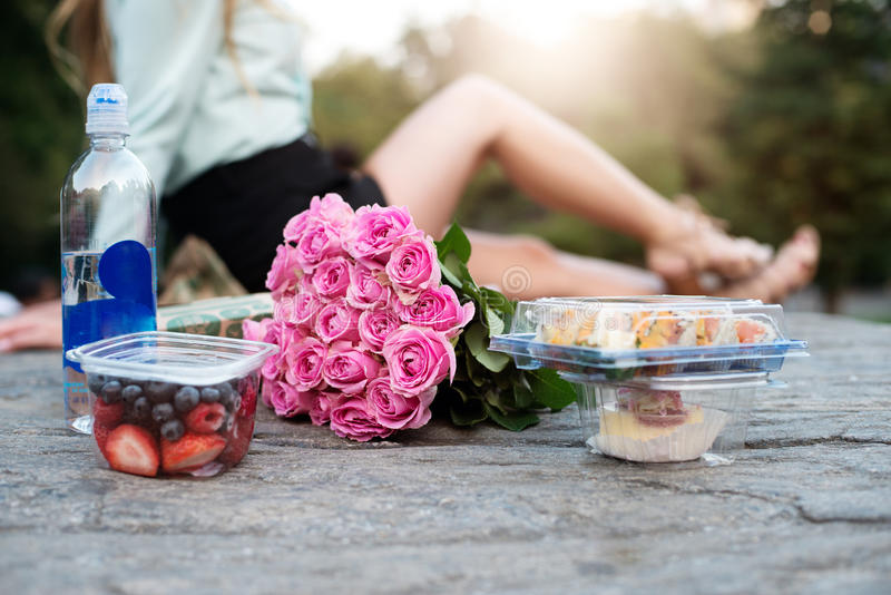 Соедините иметь романтичную дату пикника в парке с едой, пить и цветком стоковые фотографии rf