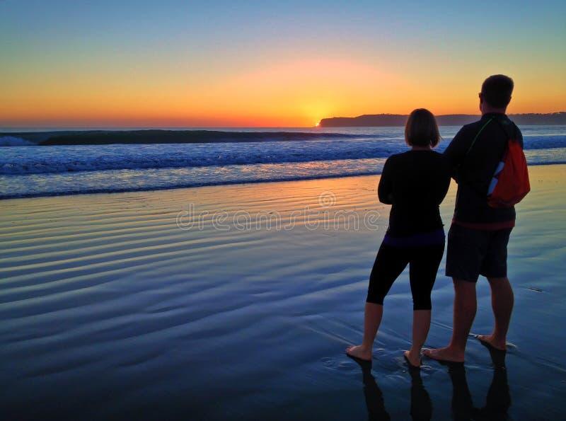 Соедините наблюдать красочный заход солнца вдоль бечевника пляжа стоковые фотографии rf