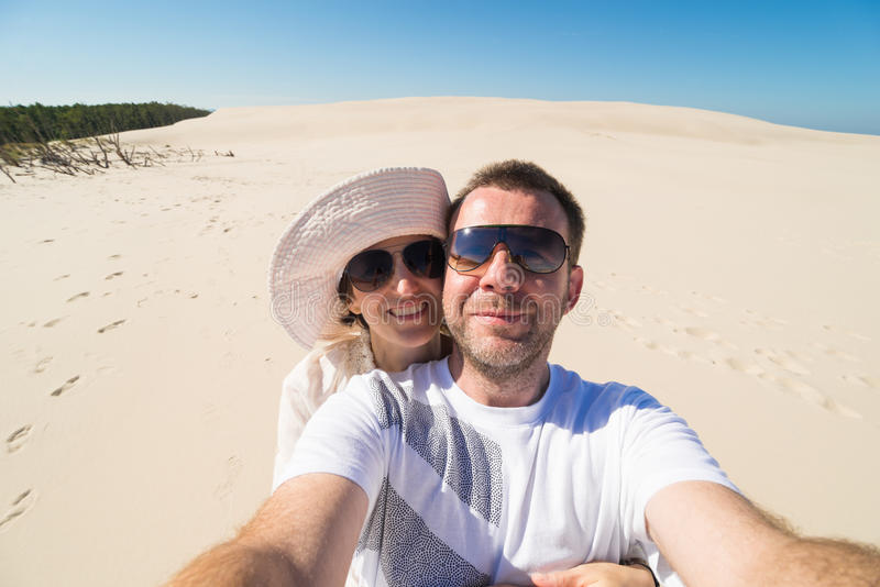Соедините принимать selfie с песком и небом в предпосылке стоковое изображение