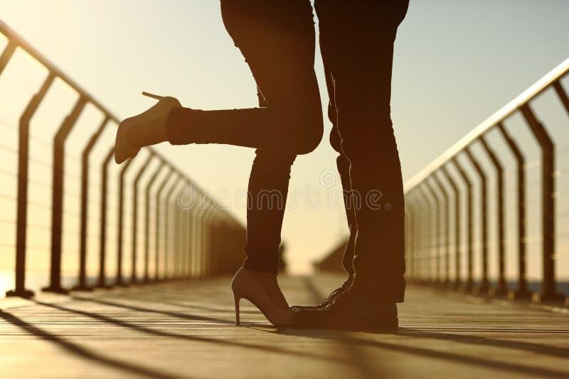 Соедините силуэт ног обнимая с влюбленностью в мосте стоковое фото